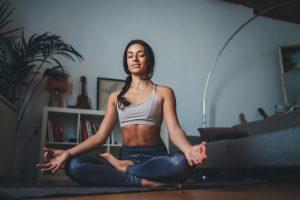 Joga - młoda kobieta ćwicząca jogę w domu.